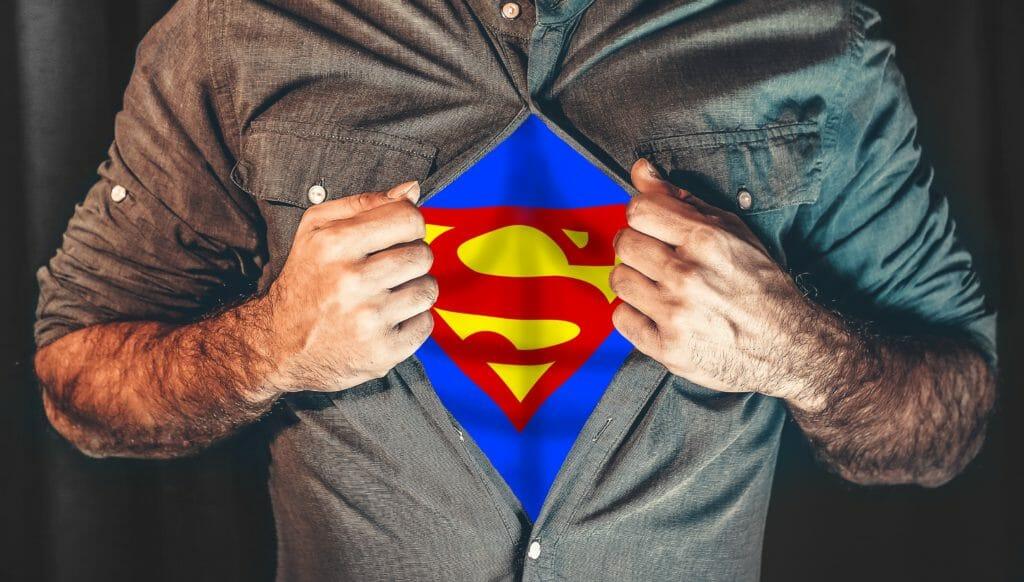 Mann hat ein Hemd an und reißt es vorne auf, zum vorschein kommt ein Superhelden Kostüm